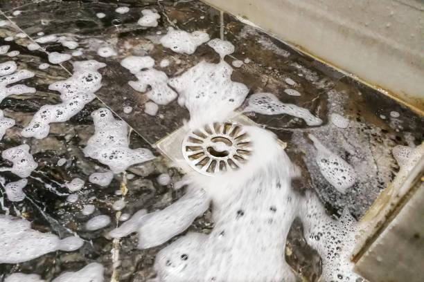 seifenschaum und wasser fließt in bad entwässerungloch - kanalisationsabflüsse stock-fotos und bilder