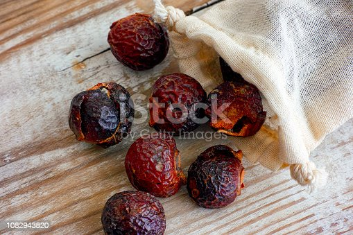 istock Soap nuts spilling from textile bag on wooden background. 1082943820