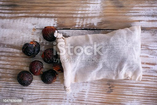 istock Soap nuts spilling from wash bag on wooden background. 1047636488