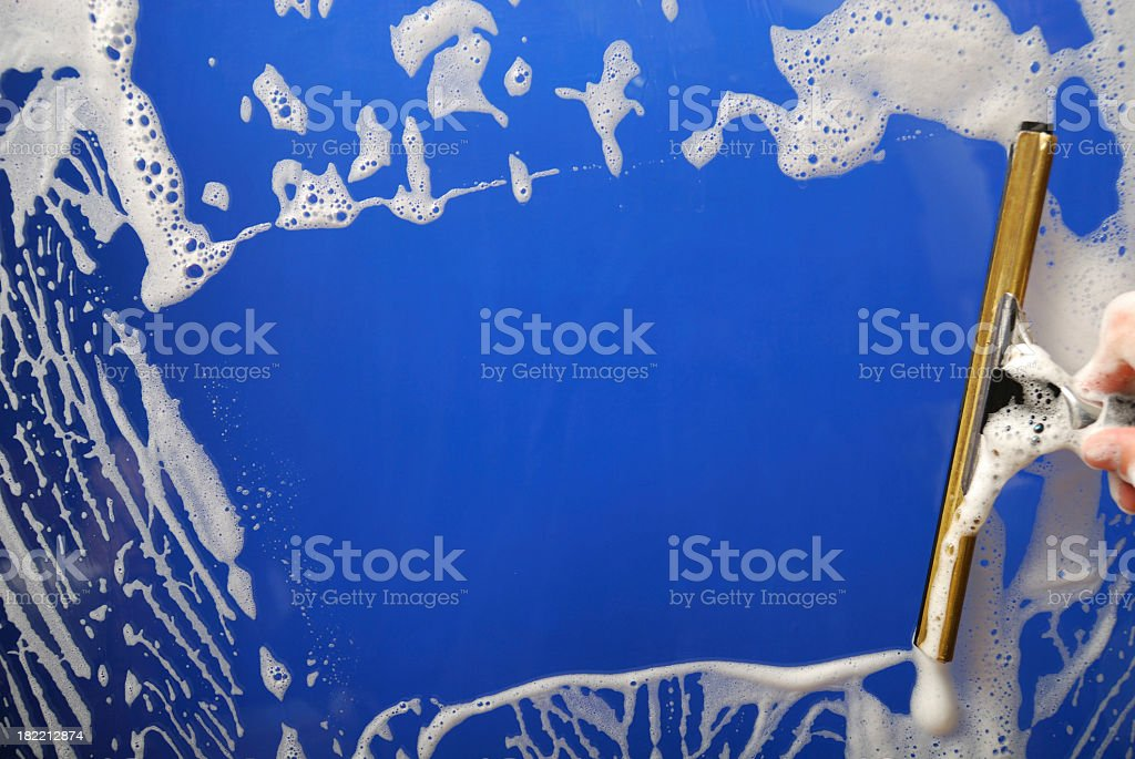 Soapy blue background being squeegeed stock photo