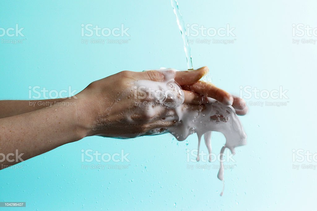 Soapy hands with suds and water on gradient blue background  stock photo