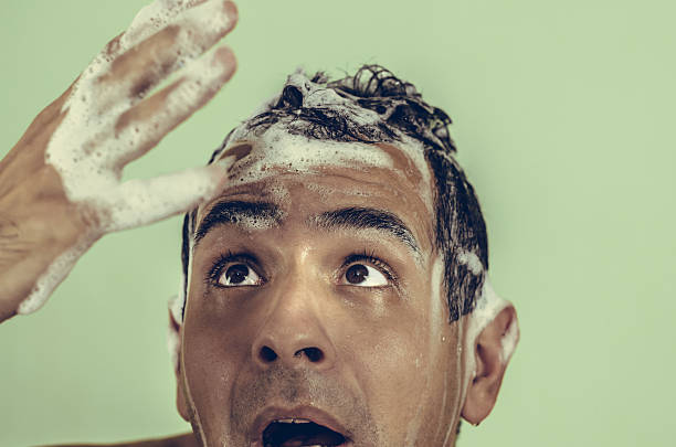 Soapy male mestizo, or mixed-looking in hand and shocked because stock photo