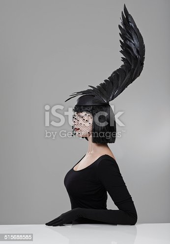 Shot of a young woman in a wing-shaped headpiece sitting in a studio
