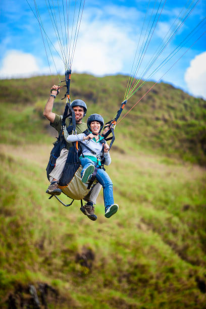 Soaring - Young couple doing tandem paragliding Real people, actual young couple doing tandem paragliding. Slight motion blur due to relative speed. paragliding stock pictures, royalty-free photos & images