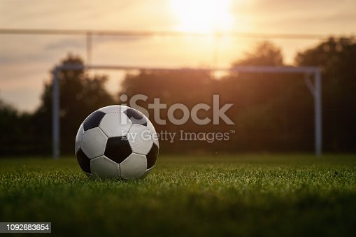 Soccer ball with player in the sunset, soccer gate in the background