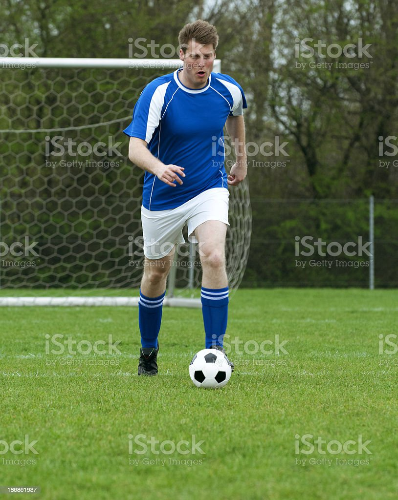 Soccer action as football player runs with the ball royalty-free stock photo