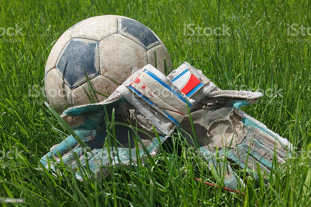 Soccer ball and goalkeeper gloves on grass stock photo