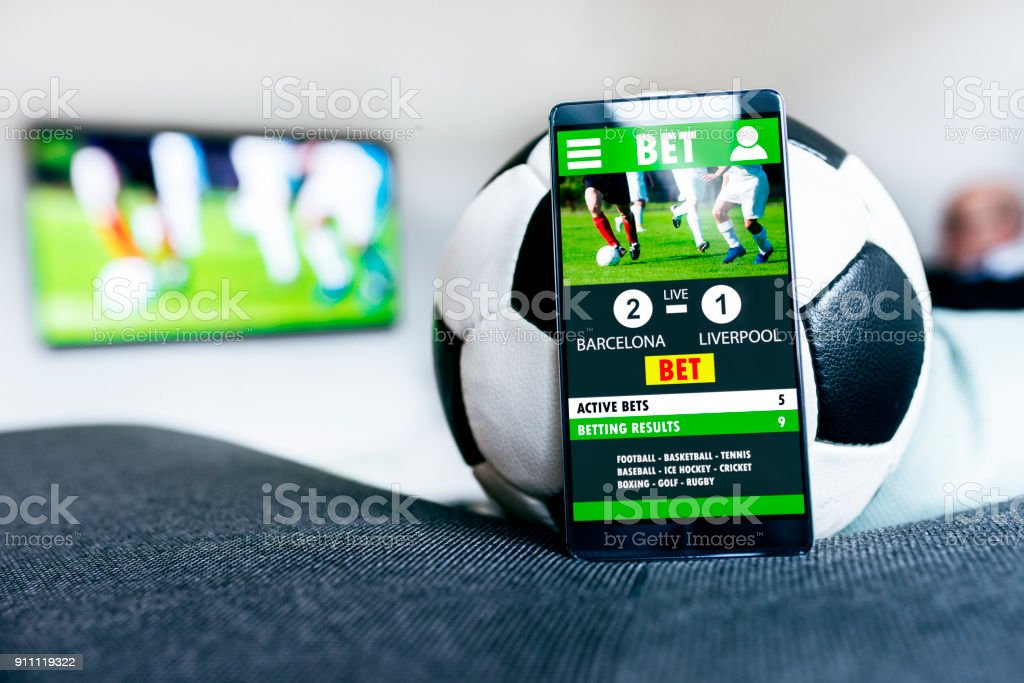 Soccer ball and mobile phone with betting app side by side stock photo