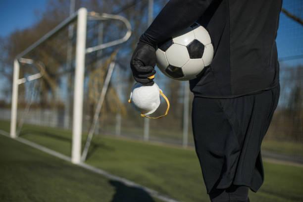 de bal en het virusmasker van het voetbal - internationale voetbal stockfoto's en -beelden