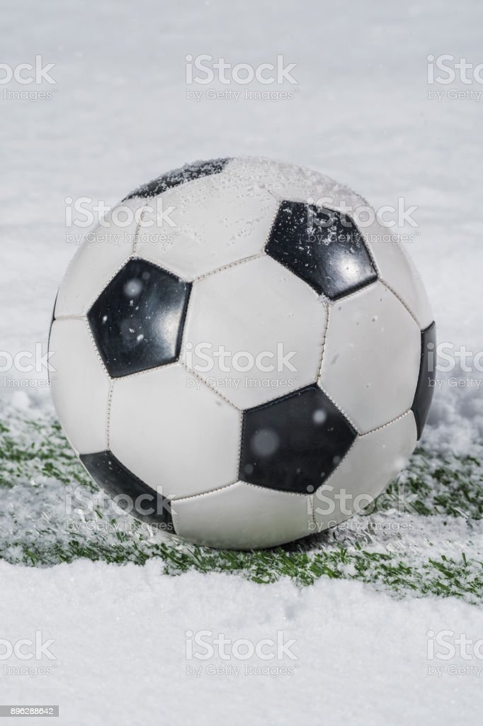 Soccer ball covered in snow sitting on a yard line cleared of snow stock photo