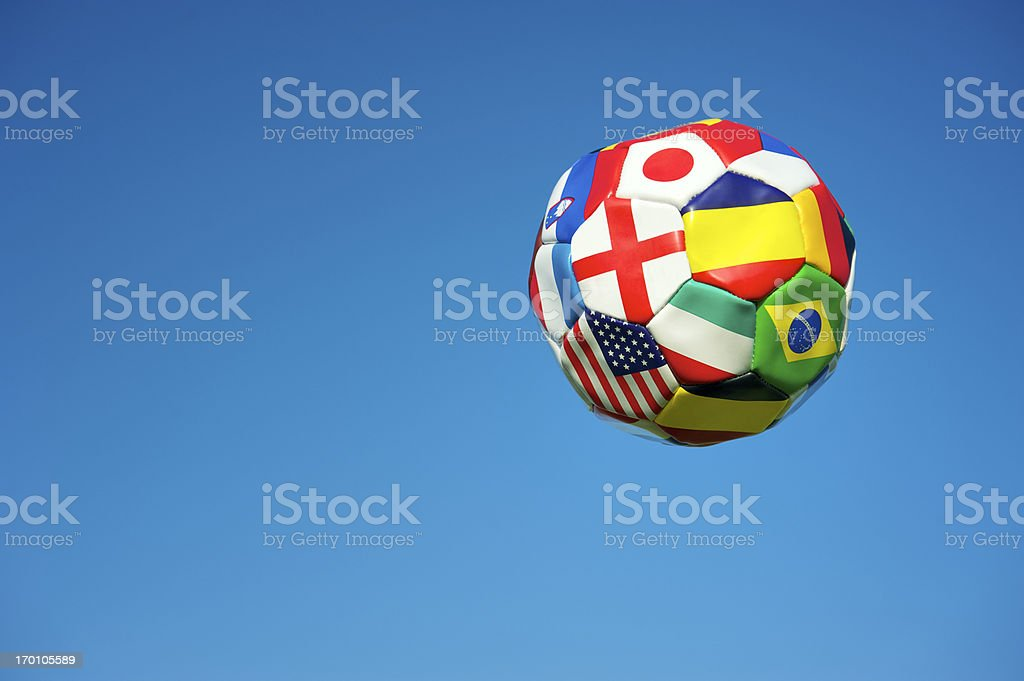 Soccer ball football with flags of many countries floats in bright...