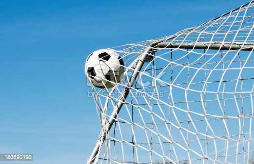 Soccer ball moves through the air and hits the goal. It's placed perfectly in the upper corner. Blue sky as background.