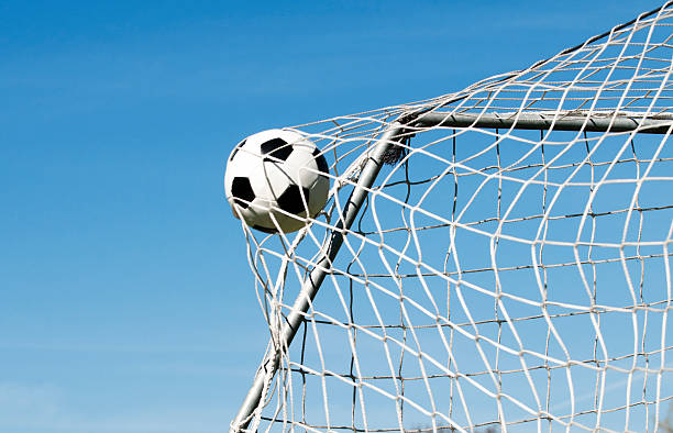 Soccer ball hits the net and makes a goal Soccer ball moves through the air and hits the goal. It's placed perfectly in the upper corner. Blue sky as background. netting stock pictures, royalty-free photos & images