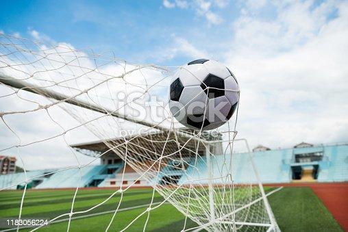 istock Soccer ball hitting the net 1183056224