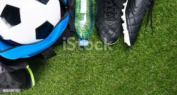 istock soccer ball in a blue bag, boots, a bottle of water and a sporty T-shirt, against the background of grass 969465182