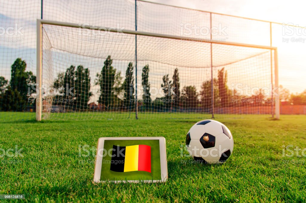 Soccer ball in front of empty goal and flag of Belgium on digital tablet on the grass stock photo