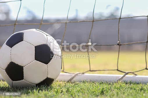 Soccer ball in goal net on grass stadium on college or high school campus. No people.  Daytime.