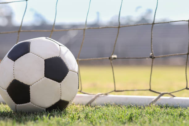 Soccer ball in goal net on stadium field on school campus. stock photo