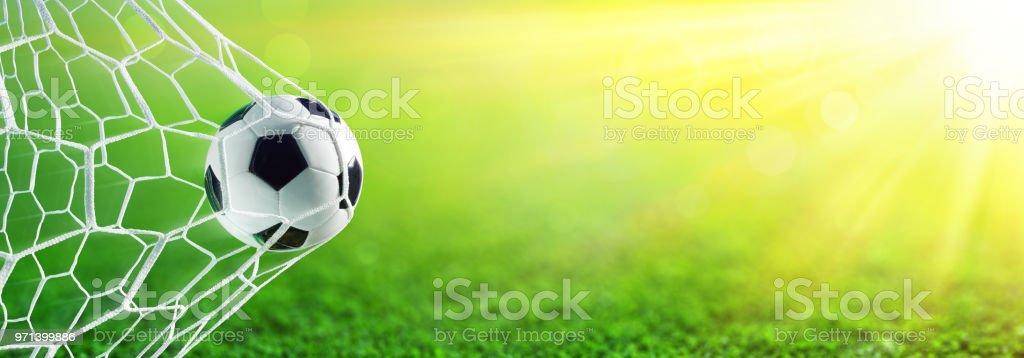 Ballon de soccer dans le but avec la lumière du soleil - Photo