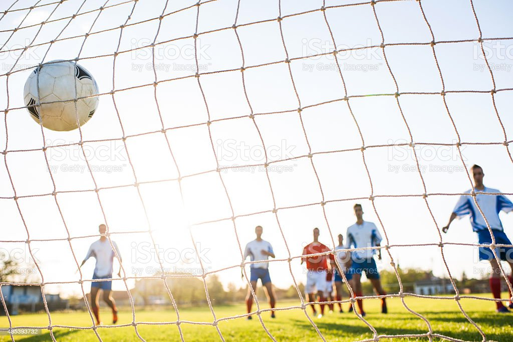 Soccer ball in goalkeeper's net. stock photo