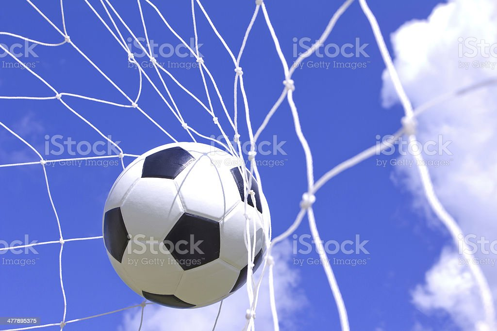 soccer ball in net on blue sky royalty-free stock photo