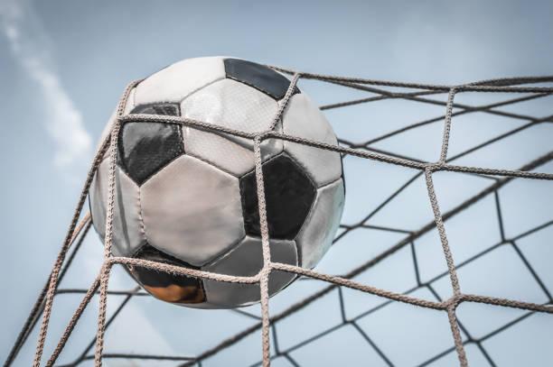 soccer ball in het doel net met blauwe hemel achtergrond - soccer goal stockfoto's en -beelden