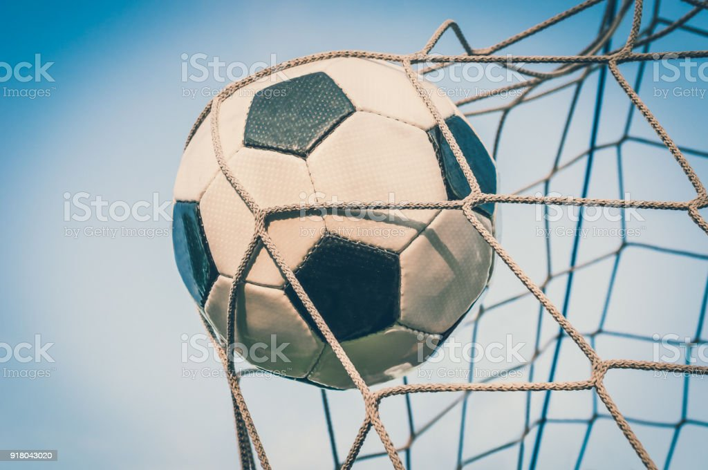 Soccer ball in the goal net with blue sky background stock photo