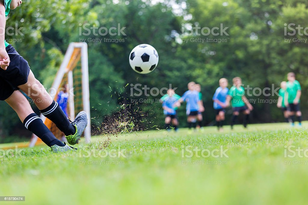 Soccer ball is in mid air while player takes shot – Foto