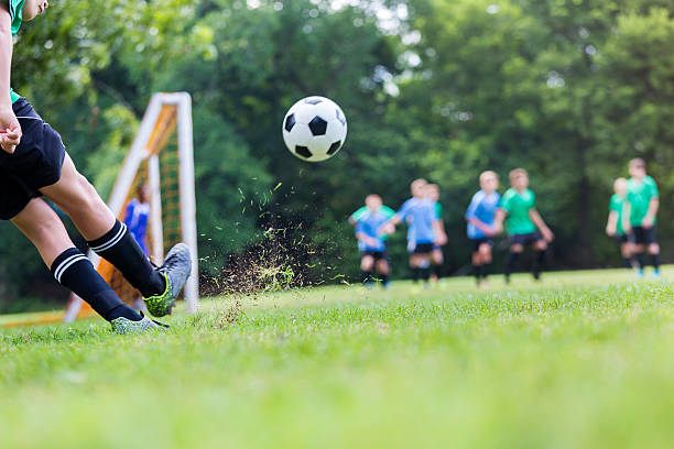 Soccer ball is in mid air while player takes shot stock photo