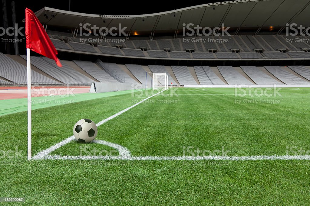 A soccer ball next to a flag on a field stock photo