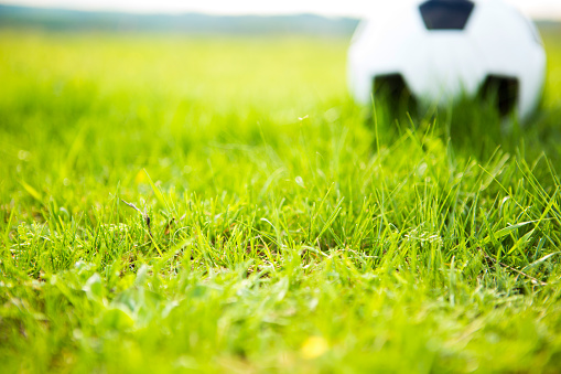 Soccer ball on a green lawn close up against clear blue sky and sun