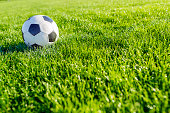 Photo of Traditional soccer ball on green  soccer field during bright sunny day.