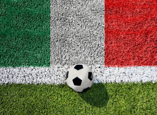 Soccer ball on green grass with Italian flag stock photo