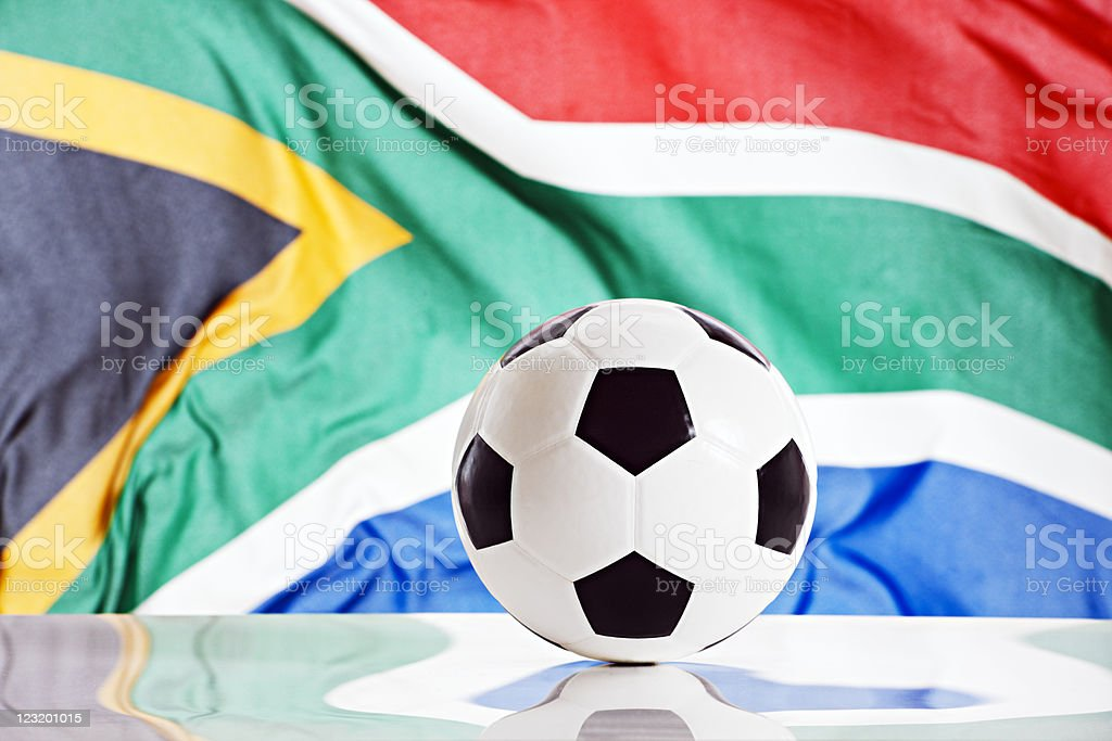 Soccer ball on reflective surface against South African flag royalty-free stock photo