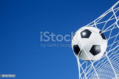 Soccer ball on the goal net against blue sky background