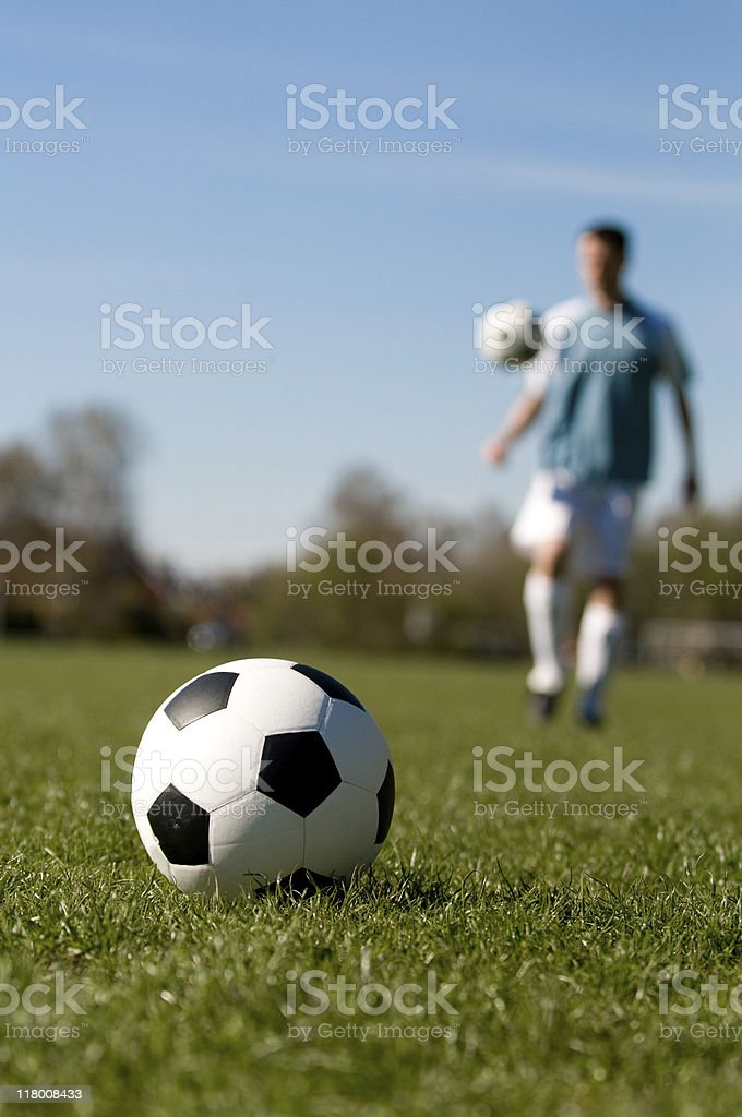 Soccer ball on the grass with player juggling royalty-free stock photo
