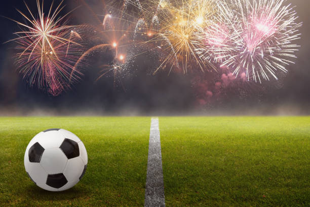 soccer ball on the green field with fireworks background - soccer league stock pictures, royalty-free photos & images