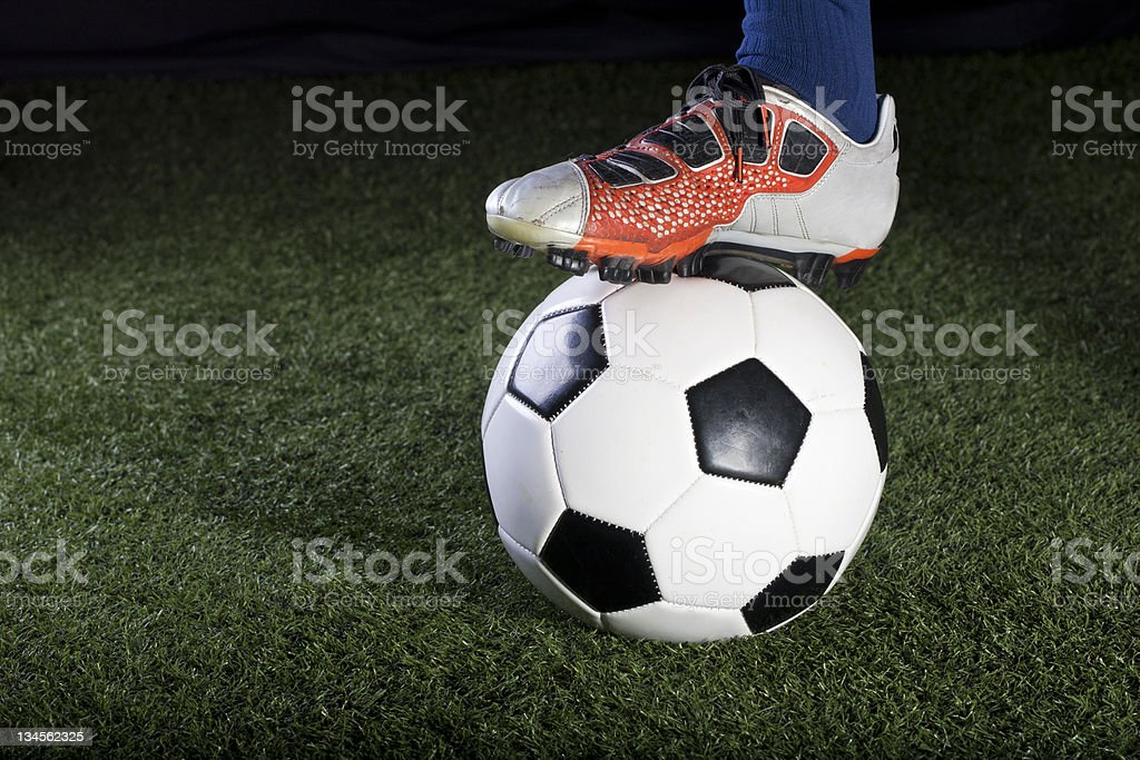 Soccer ball resting on a grass field at night royalty-free stock photo
