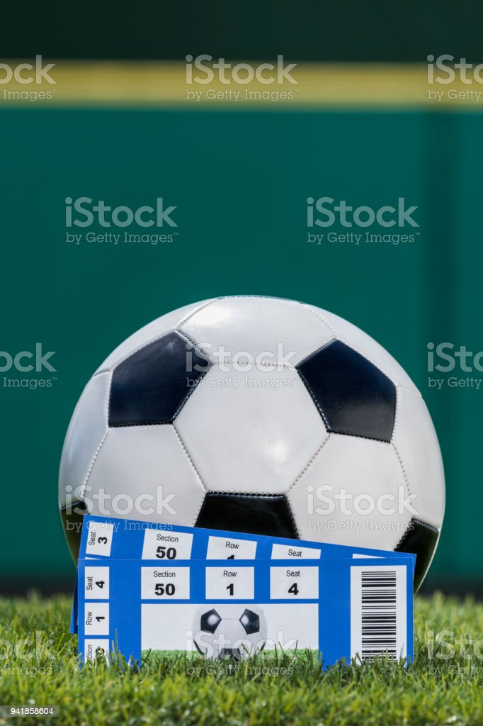 Soccer ball with 2 ticket stubs in grass of stadium stock photo