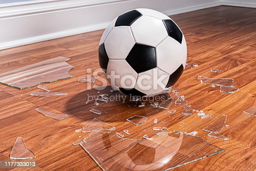 A soccer ball sitting among pieces of a broken window glass that are on the wood floor inside a home.