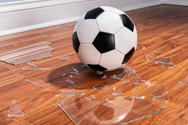 A soccer ball with broken glass from a window on the floor