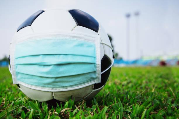 voetbalbal met medisch masker in het lege stadion. covid-19 verspreiding uitbraak - internationale voetbal stockfoto's en -beelden