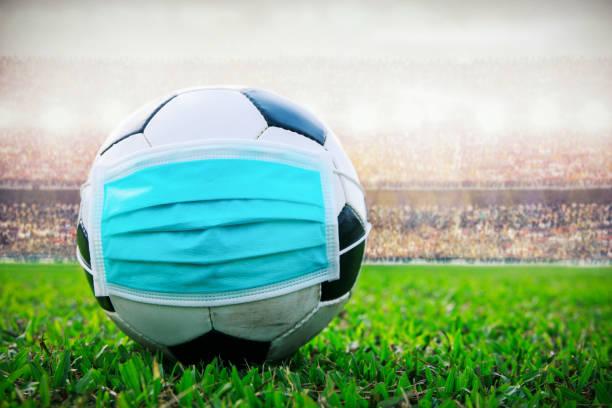 pelota de fútbol con máscara médica en el estadio. Todo evento de pausa de fútbol descanso. covid-19 propagando el brote - foto de stock