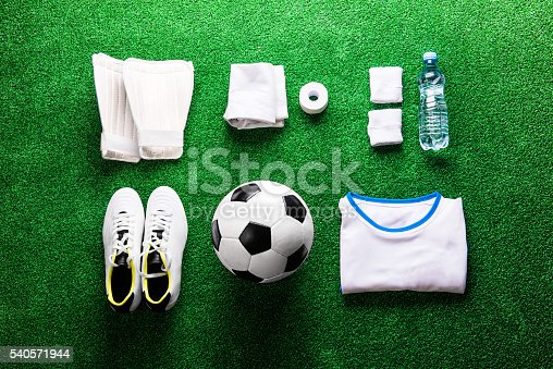 istock Soccer ball,cleats and various football stuff against artificial 540571944