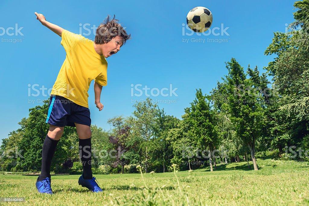 Soccer Boy Hits a Soccer Ball on Field stock photo