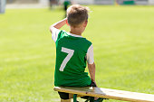 istock Soccer boy in grean jersey shirt sitting on wooden bench 1202131799