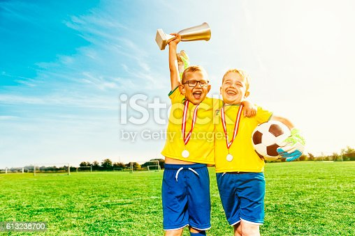 istock Soccer boys celebrate victory with medals and football 613238700