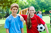 Teenage brother and sister or soccer friends kid around before soccer practice. The girl has her arm on the boy's shoulder and is holding a soccer ball. She has long blond hair in a ponytail across her shoulder. She is wearing a bright red jersey. The boy is wearing a blue jersey and has short brown hair. They are both smiling. Players are on the field in the background along with the soccer goal.