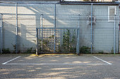 Soccer cage in the city, iron gate protection grid with soccer court behind it, empty soccer goal