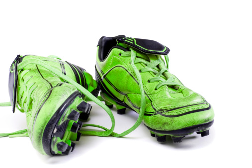Green soccer cleats isolated on white background.